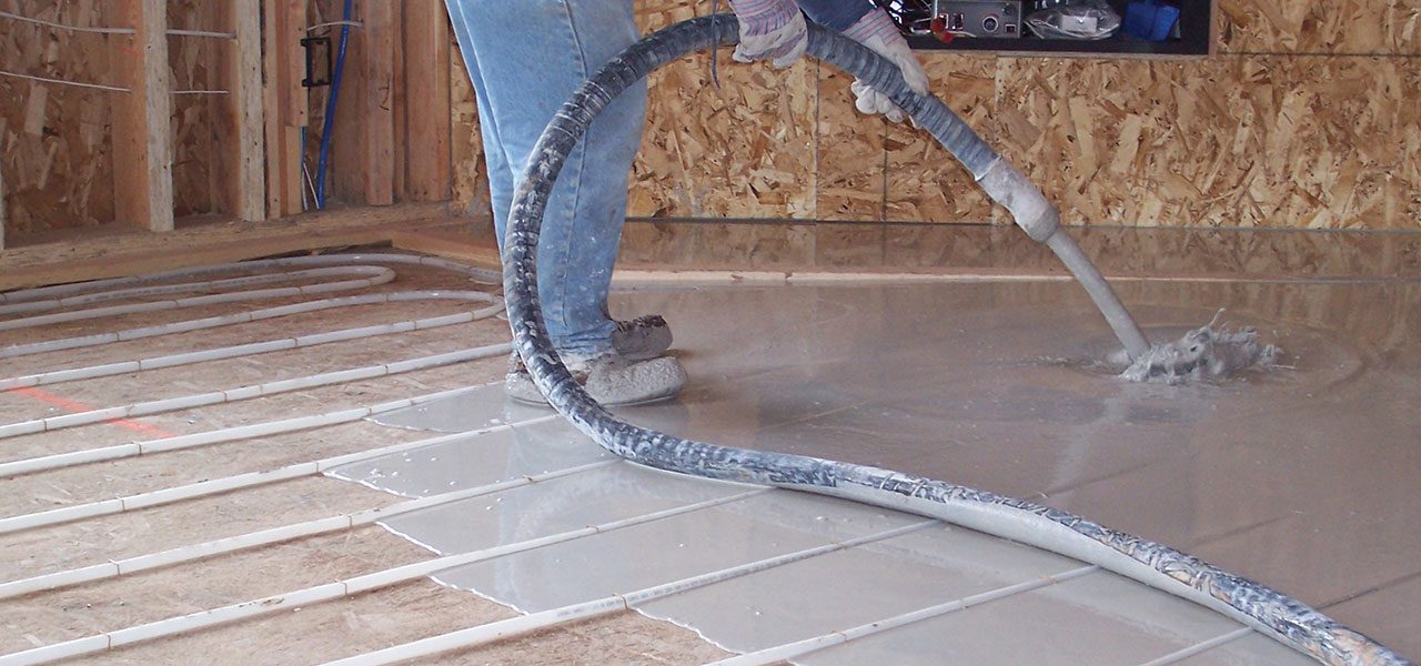 concrete being poured over heating tubes in a home under construction